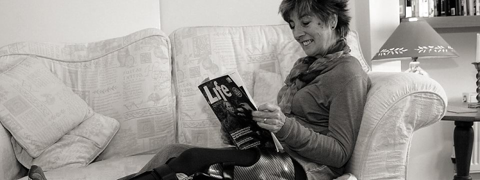 Jane relaxes on the sofa wearing her E-Mag Active orthosis.